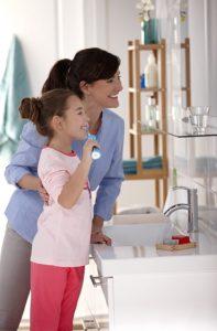 Mutter und Tochter vor Spiege beim Zaehneputzen