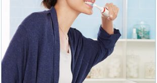 Frau putzt sich die Zähne im Bad